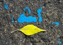 Hoja amarilla en el camino cerca de un punto azul imagen de archivo