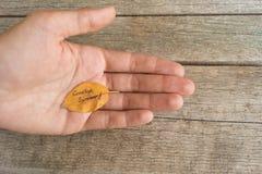 Hoja amarilla o anaranjada con VERANO de la inscripción ADIÓS en la mano femenina del ` s en el fondo de madera Fotos de archivo libres de regalías