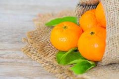 Hoja anaranjada y anaranjada en bolso del saco en fondo de madera de la tabla Foto de archivo libre de regalías