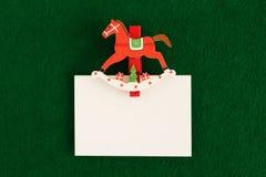 Hoja blanca con el perno de madera rojo y blanco en el fondo verde para los saludos de la Navidad Imagen de archivo