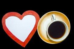 Hoja a cuadros, una taza de café sólo y un corazón imagenes de archivo