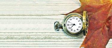 Hoja de arce del otoño con el reloj de bolsillo del vintage en fondo de madera rústico Composición de la caída Fondo del tiempo d Fotos de archivo libres de regalías