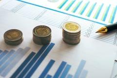 hoja de cálculo financiera de la acción de actividades bancarias con la moneda y la pluma, CRNA de la pila Fotografía de archivo