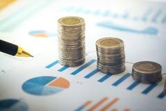 Hoja de cálculo financiera de la acción de actividades bancarias con la pila de la moneda y de la pluma o Fotos de archivo
