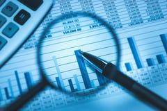 Hoja de cálculo de la contabilidad empresarial con la calculadora y pluma a través de la lupa en el azul del negocio, macro del p Fotografía de archivo libre de regalías
