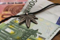 Hoja de la suspensión de la marijuana, billetes de banco euro en una tabla de madera Foto de archivo libre de regalías