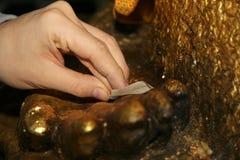 Hoja de oro del dorado a Buda para la adoración Foco selectivo Imagen de archivo