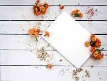 Hoja de papel blanca con el espacio para el texto con las flores y el polvo anaranjados del oro Visión superior Mesa femenina Un  Fotografía de archivo