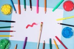 Hoja de papel blanca en un fondo azul con un lugar a inscribir alrededor de los pintores y de los cepillos, amarillo GR del color imagenes de archivo