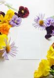 Hoja de papel blanca rodeada con las flores coloridas Imagen de archivo libre de regalías