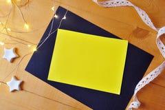 Hoja de papel del amarillo del fondo de la Navidad con el lugar para su texto y estrella y guirnalda de la Navidad blanca en un o Fotografía de archivo
