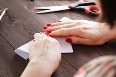 Hoja de papel del doblez de la mujer mientras que haga la papiroflexia Imágenes de archivo libres de regalías