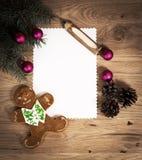 Hoja de papel en blanco en el piso de madera con un lápiz y las decoraciones de la Navidad Fotografía de archivo