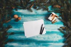 Hoja de papel en blanco en una tabla de madera azul con los artículos de la Navidad Imagenes de archivo