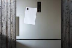 Hoja de papel vacía en puerta del refrigerador - delante de la pared de madera foto de archivo