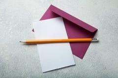 Hoja de papel vacía y un sobre con un lápiz en un escritorio blanco del vintage fotos de archivo libres de regalías