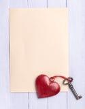 Hoja de papel vacía con un corazón del vintage y una vieja llave Foto de archivo libre de regalías
