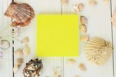 Hoja de papel y conchas marinas amarillas en un fondo de madera Fondo del recorrido Foto de archivo