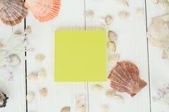 Hoja de papel y conchas marinas amarillas en un fondo de madera Fondo del recorrido Imágenes de archivo libres de regalías