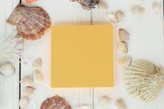 Hoja de papel y conchas marinas anaranjadas en un fondo de madera Fondo del recorrido Imagen de archivo