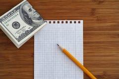 Hoja de papel y lápiz en blanco con cientos dólares de cuenta encendido Imágenes de archivo libres de regalías