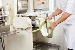 Hoja de Processing Spaghetti Pasta del cocinero en máquina Imagen de archivo