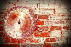 Hoja de sierra circular en una pared de ladrillo sucia Foto de archivo libre de regalías