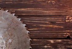 Hoja de sierra del metal en un fondo de madera Foto de archivo libre de regalías