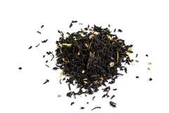 Hoja de té negra con la flor en el fondo blanco imagenes de archivo