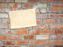 Hoja de un papel, colgando en una pared de ladrillo Imágenes de archivo libres de regalías