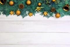 Hoja del pino con la decoración de la bola de la estrella y de la Navidad del oro amarillo encendido Fotografía de archivo
