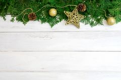 Hoja del pino con la decoración de la bola de la estrella y de la Navidad del oro amarillo encendido Foto de archivo libre de regalías