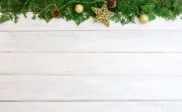 Hoja del pino con la decoración de la bola de la estrella y de la Navidad del oro amarillo encendido Foto de archivo