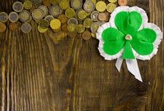 Hoja del trébol y muchas monedas en fondo de madera Copie la goma imagenes de archivo