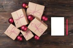 Hoja en blanco blanca con los regalos de Navidad en la opinión superior del fondo de madera, endecha plana Lista de regalo de la  Fotografía de archivo