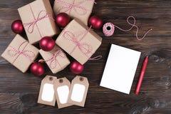Hoja en blanco blanca con los regalos de Navidad en la opinión superior del fondo de madera, endecha plana Lista de regalo de la  Imagenes de archivo