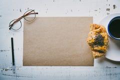 Hoja en blanco del arte de la maqueta del papel, de la pluma, de los vidrios del ojo y de la taza de café vacíos de la mañana con Fotografía de archivo