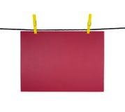 Hoja en blanco roja en la cuerda para tender la ropa para su aviso Imagen de archivo libre de regalías