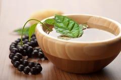 Hoja en tazón de fuente y granos de madera. fondo del zen Imagen de archivo