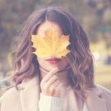 Hoja hermosa de Autumn Woman Holding Yellow Maple Foto de archivo
