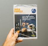 Hoja informativa de la publicidad de la familia de Ikea en la mano masculina Foto de archivo libre de regalías