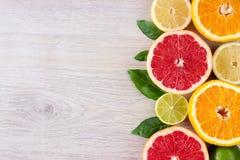 Hoja jugosa de la menta del fondo del corte de los agrios Naranjas, limones, cales, pomelo, hojas de menta en un fondo de madera  Imagen de archivo libre de regalías