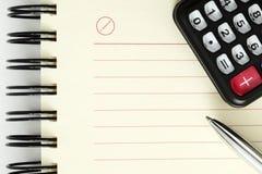 Hoja limpia del cuaderno con la pluma y la calculadora fotografía de archivo libre de regalías