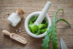 Hoja, mortero por completo del áloe tajado y botella verdes de Vera del áloe de glóbulos de la homeopatía imagenes de archivo