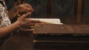 Hoja panorámica de la mujer mayor del tiro a través del texto cursivo ruso del libro en la tabla metrajes