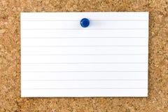 Hoja rayada blanca en blanco Cork Board Pushpin Foto de archivo libre de regalías