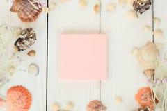 Hoja rosada a registrar y conchas marinas en un fondo de madera Fondo del recorrido Imágenes de archivo libres de regalías