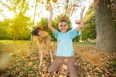 Hoja trowing del niño feliz en el parque y localización en tierra con G Fotos de archivo