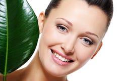 Hoja verde cerca de la cara de risa feliz de la mujer Imagen de archivo