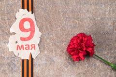 Hoja vieja con la inscripción el 9 de mayo y una cinta de San Jorge con una flor roja contra la perspectiva de un papel viejo Foto de archivo libre de regalías
